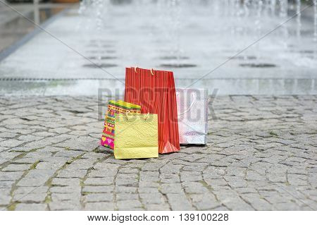 shopping bags on the pavement. fountain in the background.