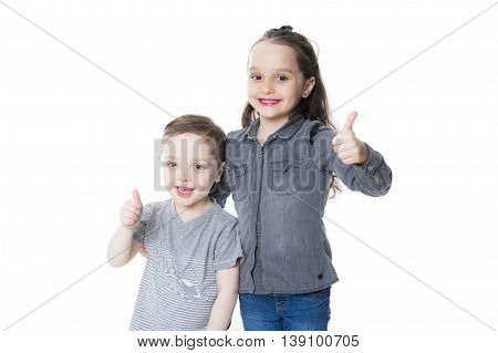 A cute little boy and girl with his thumb up on the white background