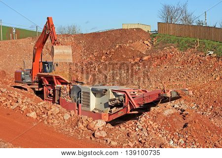 Mobile stone crusher and digger on a construction site
