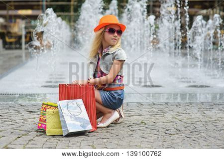 Elegant Charming cute little girl in fashionable clothes and sunglasses orange hat sitting with full shopping bags. Looking to side. Shopping bags on pavement. Fountain in background.