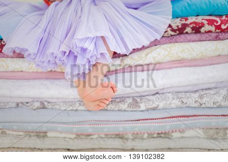 Decorations for fairy tale Princess and the Pea. Little girl with bare feet sitting on the pile of blankets and mattresses. Child in a lilac fluffy skirt at the party. Girl's birthday.