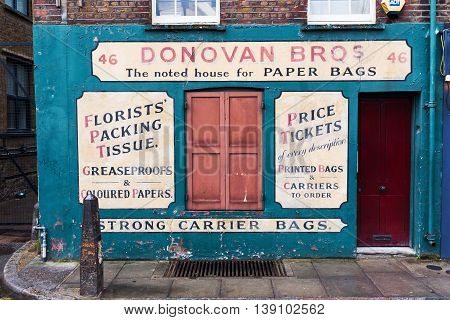 Old Building With Antique Signage Of A Paper Bag Merchant In Shoreditch, London, Uk