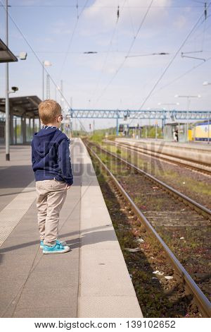Adorable kid boy waiting for a train at the railway station in a sunny day. Child ready for traveling by train. Train station. Dreaming of traveling. Sunny day at the railway station