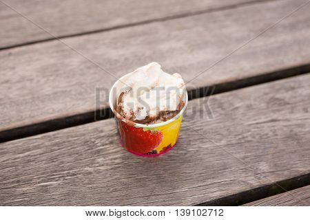 A cup of soft ice cream on the wooden background. Summer dessert on the wooden table in a cafe outdoors. Fresh scoops of assortied ice-cream. Sundae.