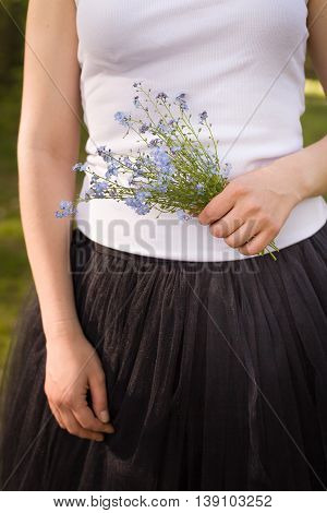 Young girl in a white tank top and black fluffy skirt holding a beautiful bouquet of forget me not flowers in her hand. Birthday flowers. Nature and beauty. Young lady with bunch of blue daisies.
