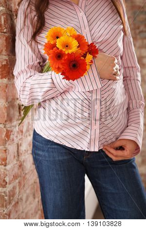 Closeup image of pregnant woman touching her belly with hands. Young pregnant woman in blue jeans and pink shirt holding bunch of bright summer flowers. Expecting a child.