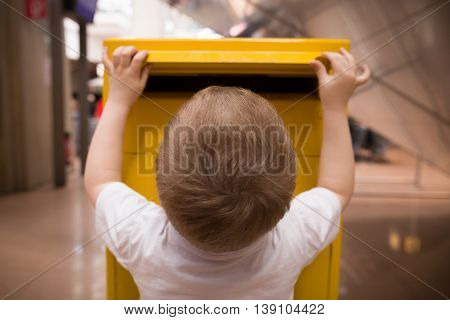 A little blond boy in a white t-shirt puts a letter into a yellow postbox. Sending post to a friend at the post office.