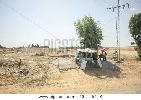 TUNIS TUNISIA - SEPTEMBER 12 2012 : Two man sitting next to a booth with food and drink on the field next to a road in TunisTunisia.