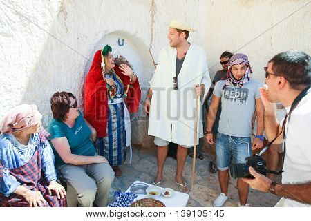 MATMATATUNISIA - SEPTEMBER 17 2012 : Couple dressed in a berber's clothing with a group of tourists in front of a troglodyte home tasting local food specialties in berber village in MatmataTunisia.