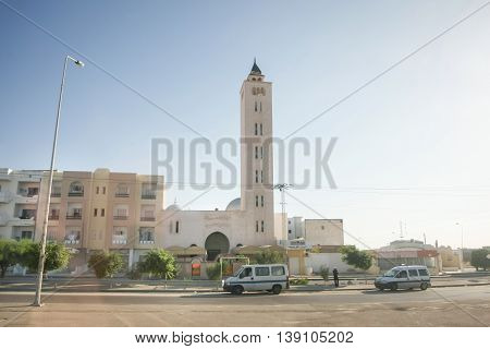 TUNISIA - SEPTEMBER 19th 2012 : A view of residential neighborhood with cars in the street and a mosque with tower in Tunisia.