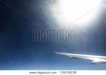 A view of the airplane wing and sunlight from the airplane.
