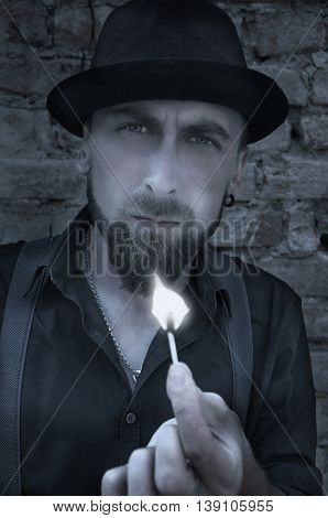 Man in darkness holding  match on brick wall background