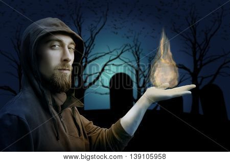 Warlock holding fire on cemetery background. Halloween concept. Gothic concept.