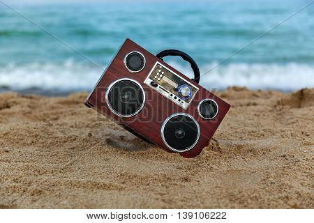 In the background of the radio recorder waves wash the shore, Radio recorder on the sand