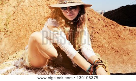 Boho style woman portrait sitting on fur, fashion hat, sunglasses and wristbands, sunny outdoor