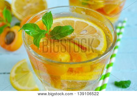 Cold Summer lemonade with peach and apricot on a blue background