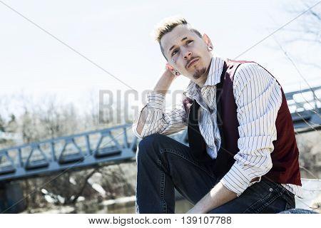 An adut outside close to a bridge