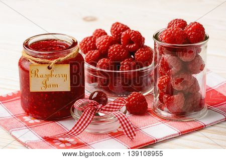 Raspberry jam in glass jar and raspberries.