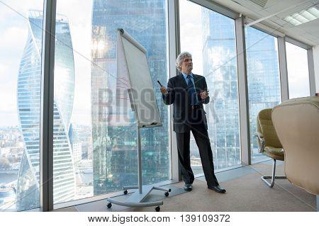 Mature business man making a presentation in modern office