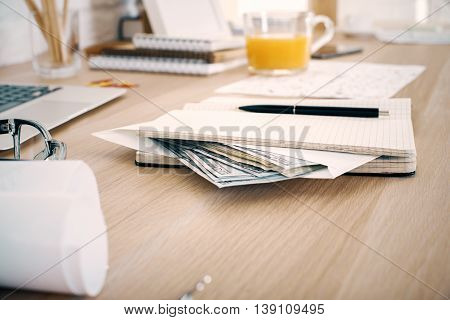 Bribery and corruption concept with dollar banknotes inside notepad on office desktop
