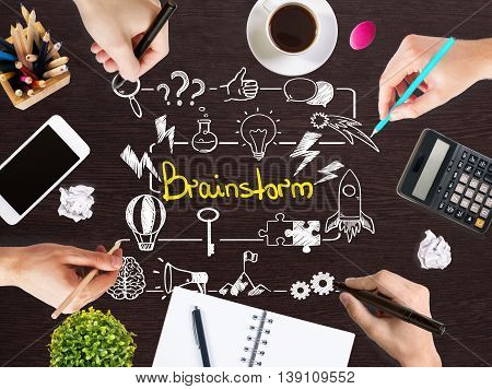 Brainstorm concept with businesspeople hands drawing sketch on wooden office desktop with blank smartphone coffee cup stationery and other items