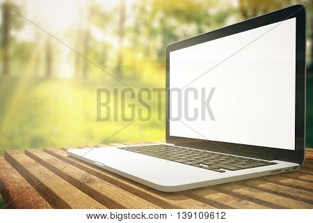 Side view of laptop with blank white screen placed on wooden plank table. Forest with sunlight in the background. Mock up 3D Rendering