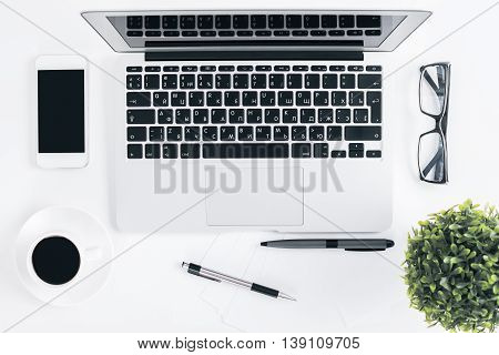 Top view of light office desktop with laptop blank cellular phone coffee cup glasses pens and decorative plant. Mock up