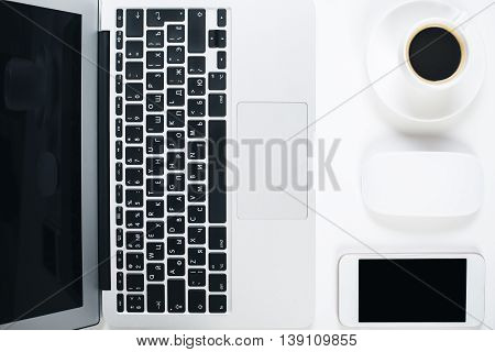 Top view of bright office desktop with blank laptop smart phone computer mouse and coffee cup on saucer. Mock up