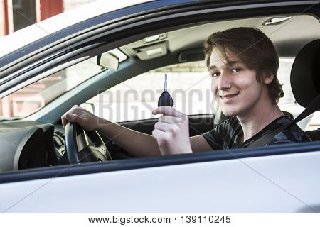 A Teenage boy and new driver behind wheel of his car