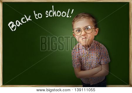 Emotional pupil boy near school chalkboard .