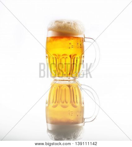 Full glass of beer with foam .