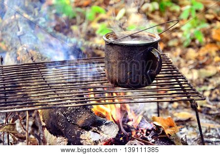 Tourist fire with a mug of boiling water on Camping.