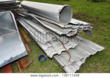 Metal parts are dismantled structures stored in the soil on the territory of industrial site.