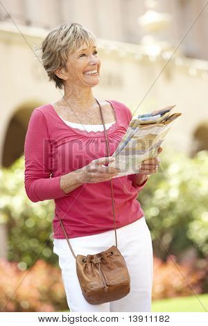 Senior Woman Walking Through City Street With Map