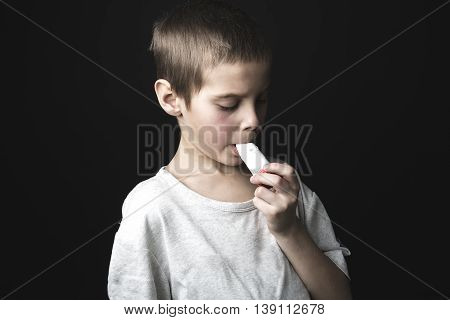 A Close up image of a cute little boy using inhaler for asthma.