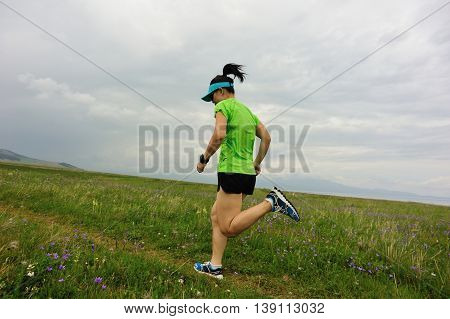 healthy young woman trail runner running on beautiful trail