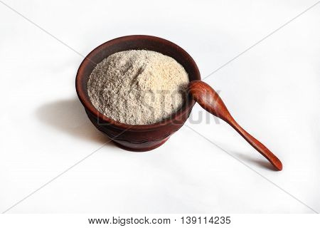 whole-wheat flour in an earthenware dish with a wooden spoon on a white background. isolated photo