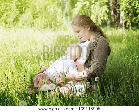 The little boy pressed his lying hugging pregnant mom in the meadow