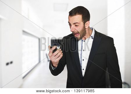 young businessman in office screaming on the phone