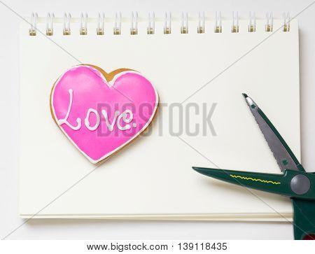 Breaking up. Scissors cutting heart on notebook. Heart surgery.