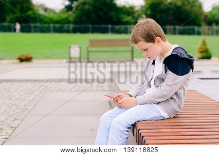Little Boy Child Playing Mobile Games On Smartphone