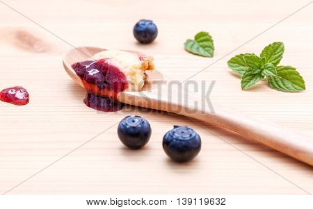 Composition Of Blueberry Cheesecake In Wooden Spoon With Fresh Mint Leaves And Ripe Blueberry On Woo