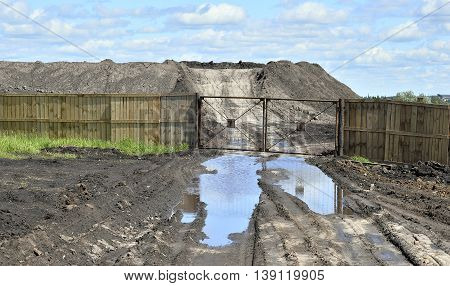 Dirt road a pool and a lot of stored in the open air ground for a closed fence