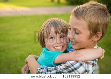Boy and girl hugging. Green meadow. Funny kids.