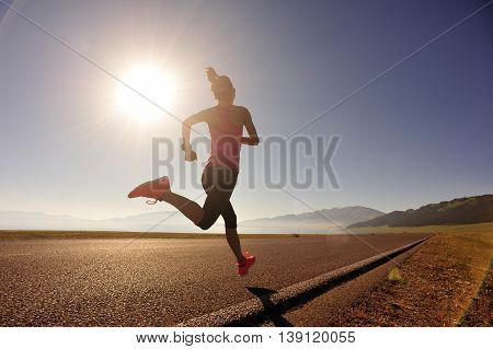 young fitness woman runner running on sunrise seaside trail
