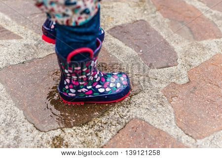 Child Wearing Rain Boots Jumping Into A Puddle