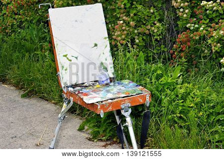 Hands of the artist with a brush paint a picture on an easel in the open air