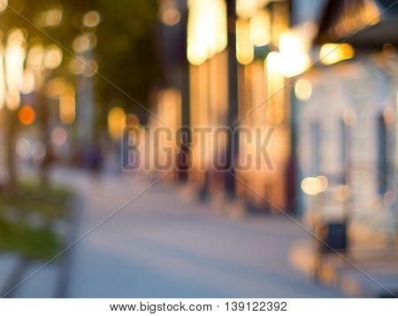 Blurred and out of focus image of streets and buildings that lit the sun at sunset.
