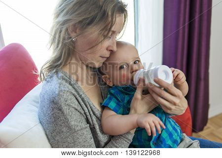 A mother feeding her adorable son at home