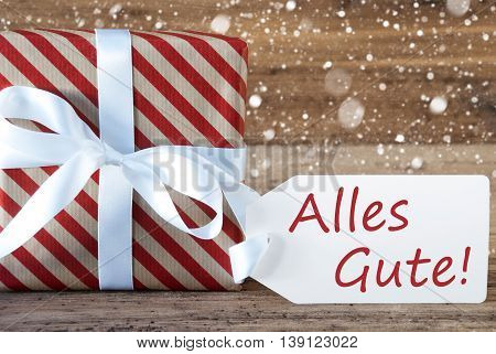 Christmas Gift Or Present On Wooden Background With Snowflakes. Card For Seasons Greetings. White Ribbon With Bow. German Text Alles Gute Means Best Wishes